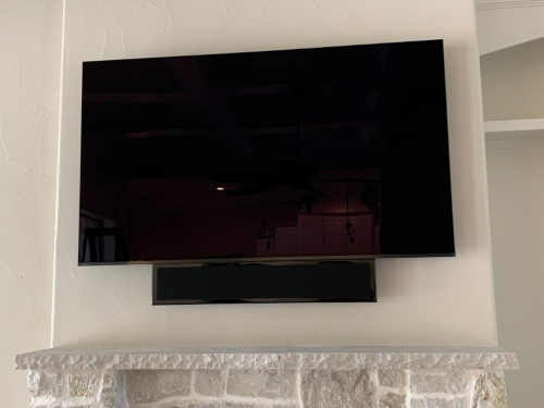 TV turned off with black screen against a white wall over the fireplace.