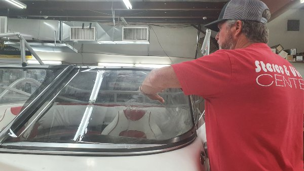 Picture of our window tinter putting window film on a boat.