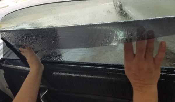 Installation of window tint on vehicle window.