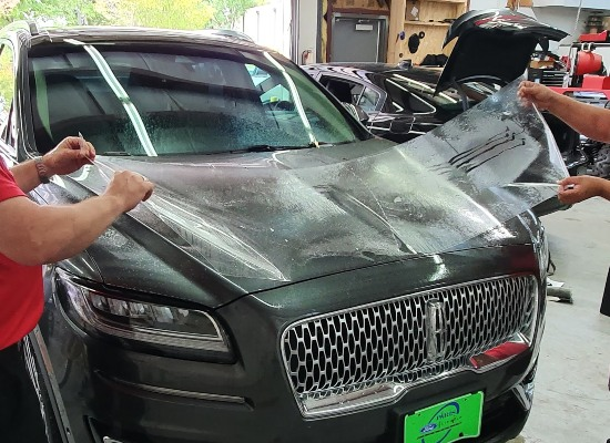 Picture of our technicians installing SunTek PPF on a 2020 Lincoln Aviator.