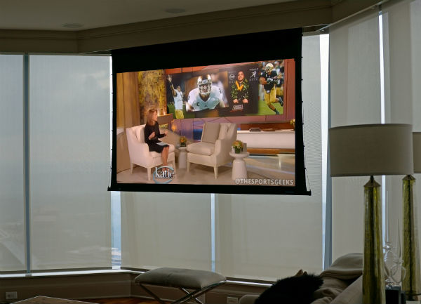 Living room turns into theater with hidden screen and motorized shades