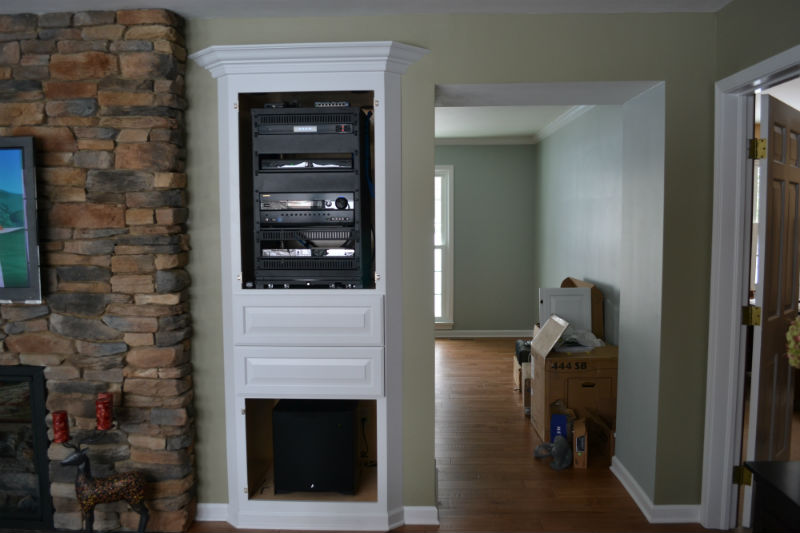 Custom home theater with a hidden rack and RTI remote control, hidden speakers and hidden subwoofer by Innovative Audio Visual, LLC in Erie, PA