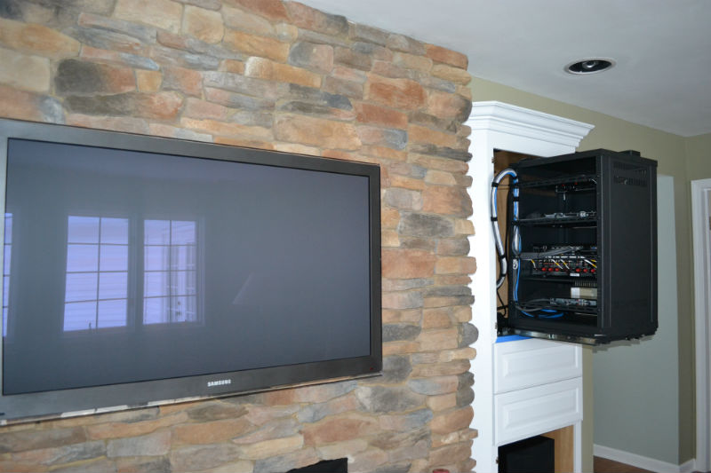 Custom home theater with a slide out rack and RTI control and custom mounted TV on a stone fireplace by Innovative Audio Visual, LLC in Erie, PA
