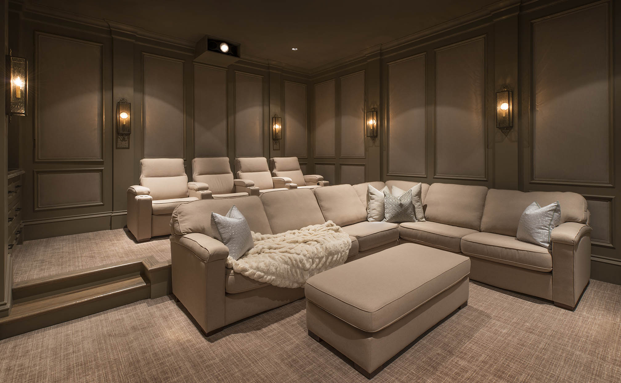 A custom home theater private cinema in Flower Mound Texas with fabric walls, sectionals and warm colors. 4K Projector, Screen Innovations Screen.