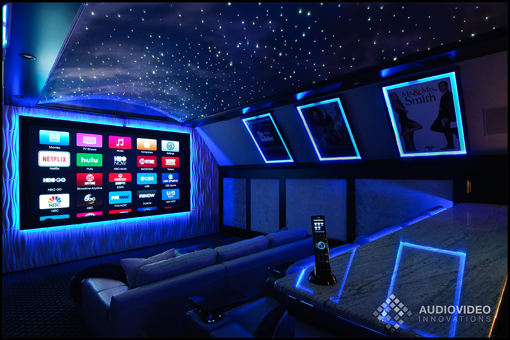 Frisco, TX Home Theater with fiber optic star ceiling and HD Projector. Blue LED lights surround movie posters and a granite bar provides additional seating.
