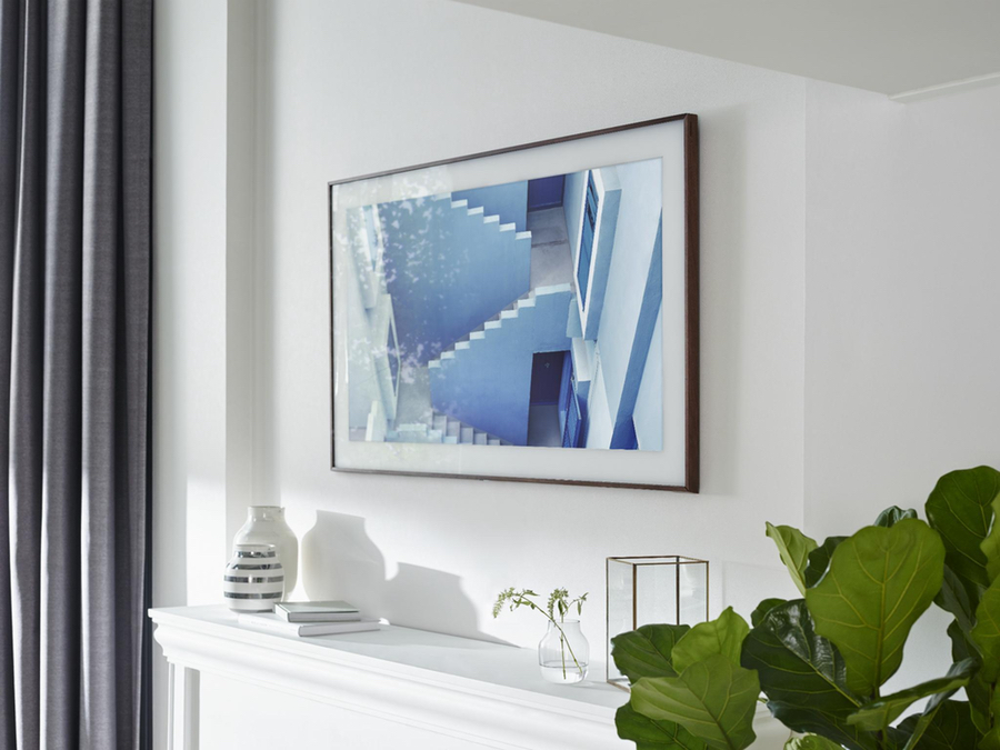 Samsung's Frame TV displaying photo realistic artwork on a white painted wall above a fireplace